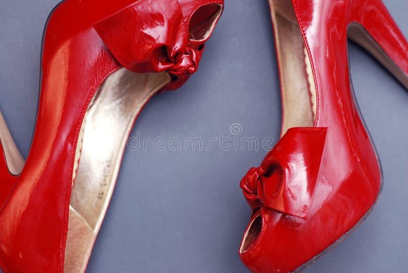 Pattini rossi delle donne dell'alto tallone Vista superiore Fondo di gray blu fotografia stock