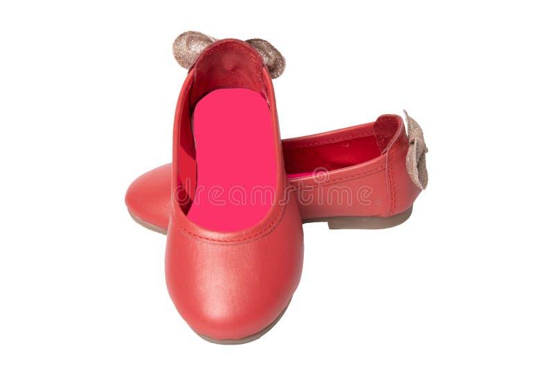 Pattini rossi Primo piano delle scarpe rosse delle ragazze con un arco dorato isolato fotografie stock libere da diritti
