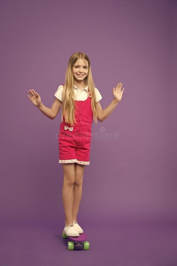 Pattino felice di giro della ragazza su fondo viola Piccolo bambino sul bordo del penny Sviluppo e felicità di infanzia immagine stock