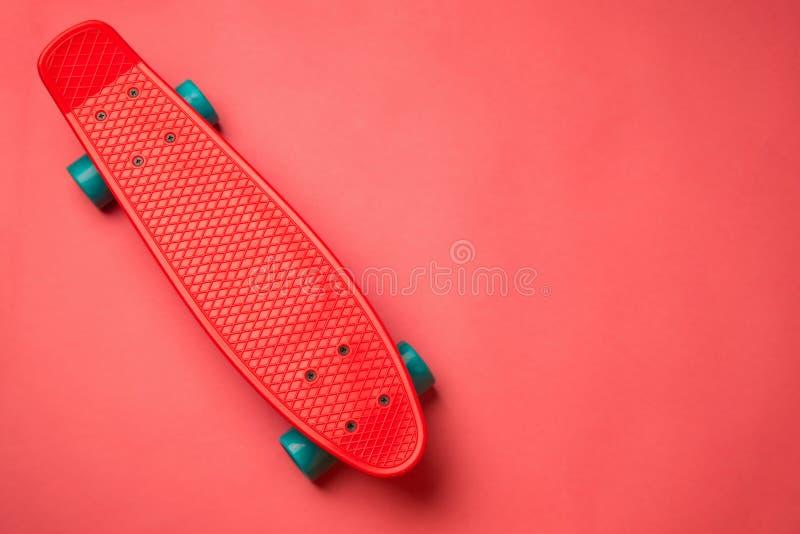 Pattino rosso con le ruote blu su fondo rosa il pastello crea immagine stock