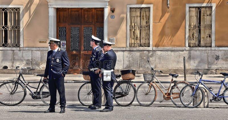 01 05 2016 Pattuglia della polizia del comune sulla via di Padova con le biciclette e di vecchia costruzione in terra posteriore, immagine stock libera da diritti