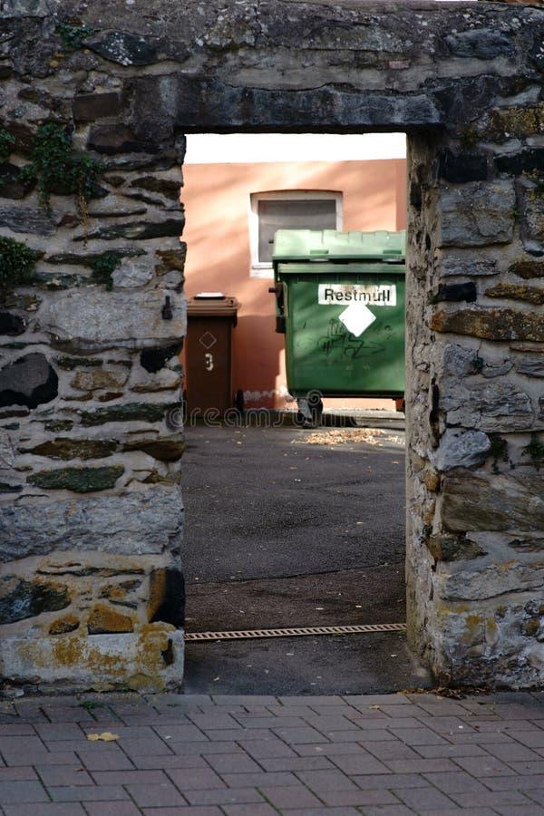 Pattumiere dietro la parete del fieldstone fotografia stock