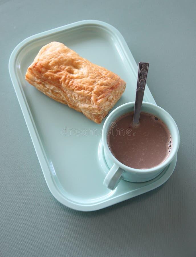 Patty und heißer Kakao in einem blauen Teller lizenzfreie stockbilder