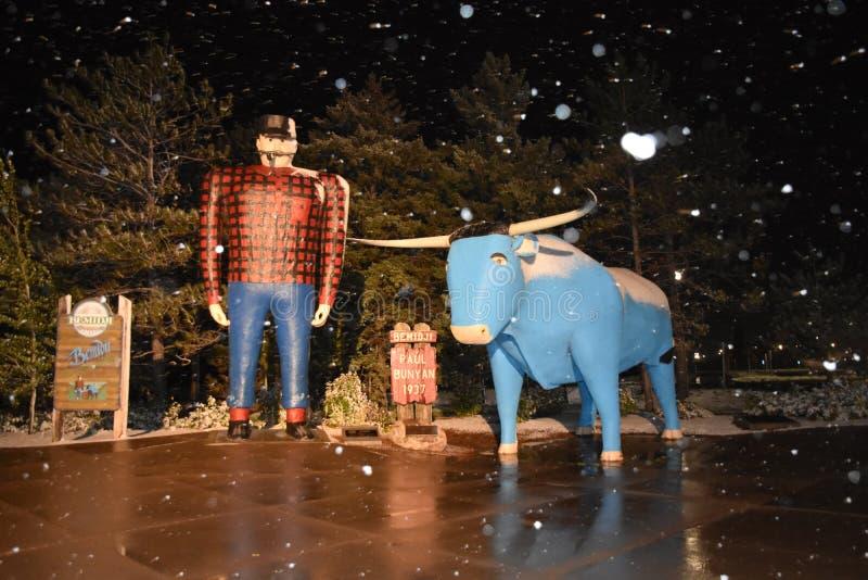 Paul Bunyan e Babe sob flurries de neve à noite foto de stock