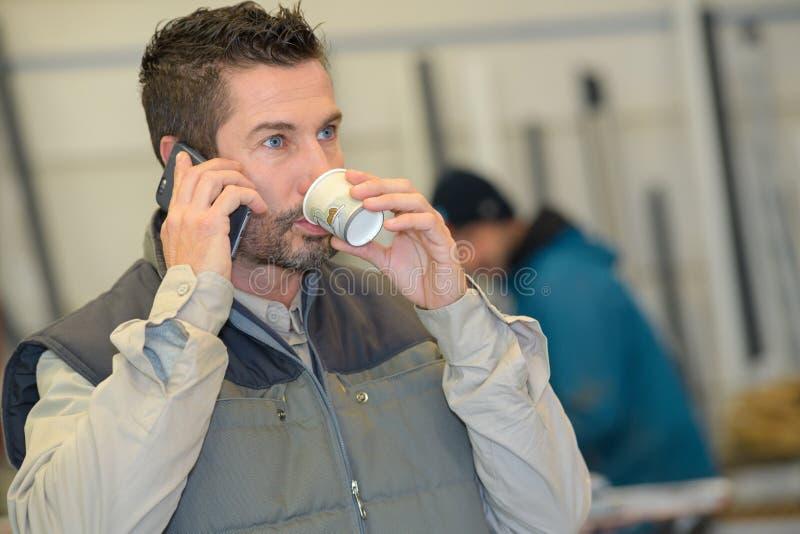 Pausa caffè dell'uomo facendo uso del telefono immagine stock