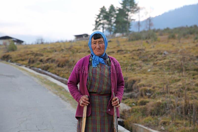 Pausas coloridas de la mujer de ella trabajo en Bhután rural imagen de archivo