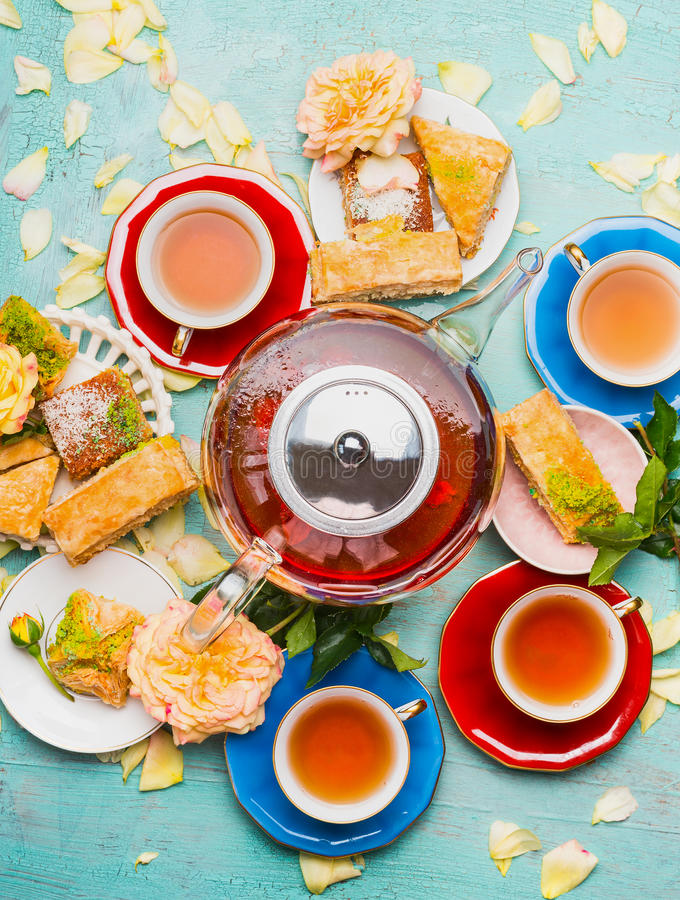 Pause café avec des tasses, des fleurs, des gâteaux et le pot de thé sur le fond bleu-clair photos libres de droits