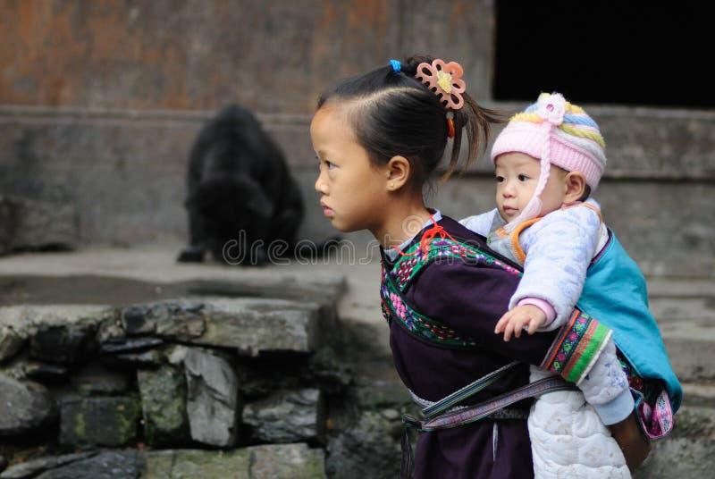 Pauvre fille traditionnelle qui s'inquiètent l'enfant dans le vieux village en Chine image stock