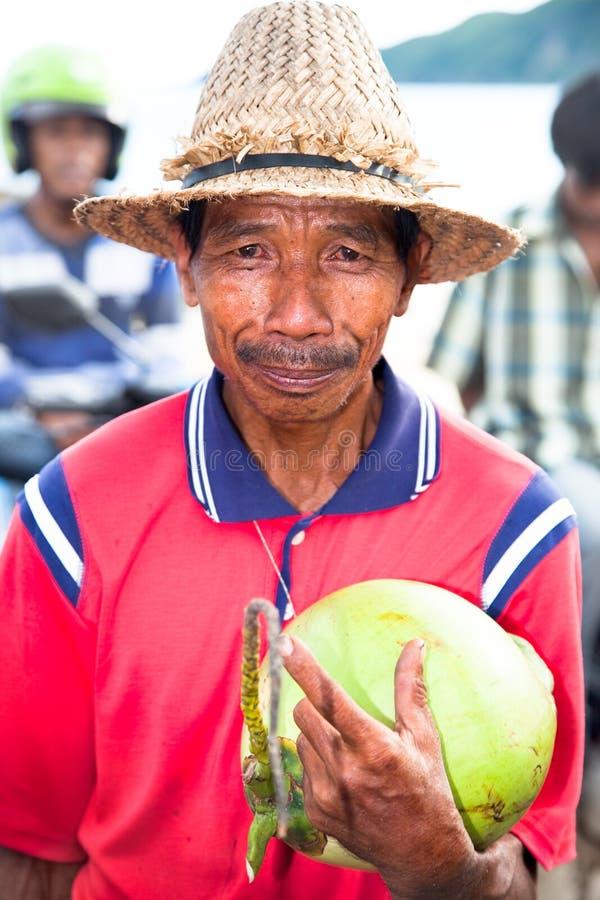 Pauvre homme avec le chapeau de staw vendant une noix de coco photo libre de droits