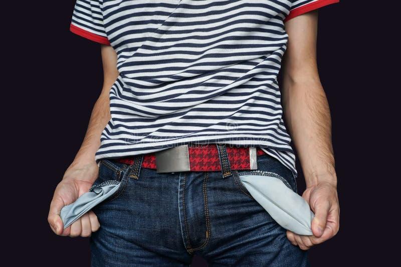 Pauvre homme dans des jeans avec la poche vide d'isolement sur le noir photos stock