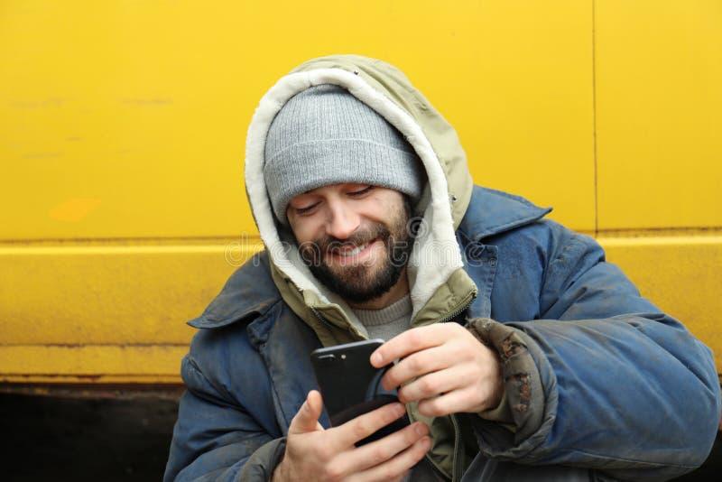 Pauvre homme sans abri avec le smartphone volé photographie stock libre de droits