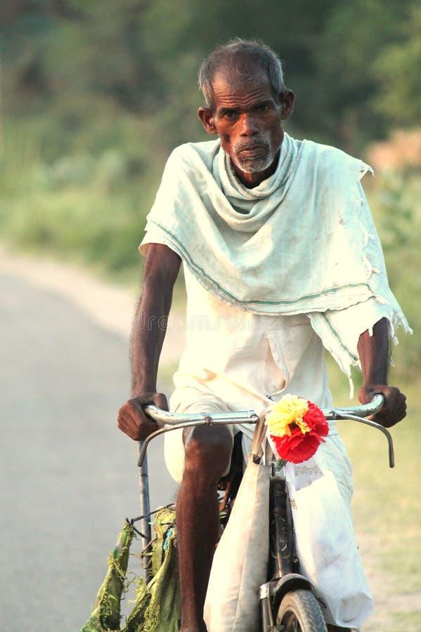 Pauvre homme sur une bicyclette image stock