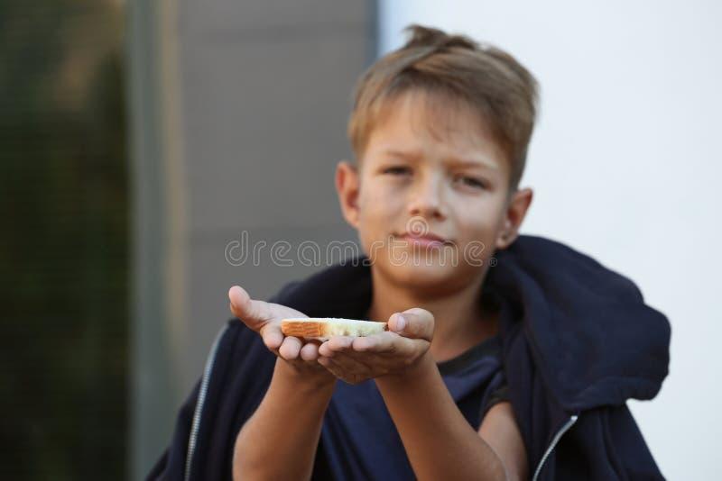 Pauvre petit garçon avec du pain image libre de droits