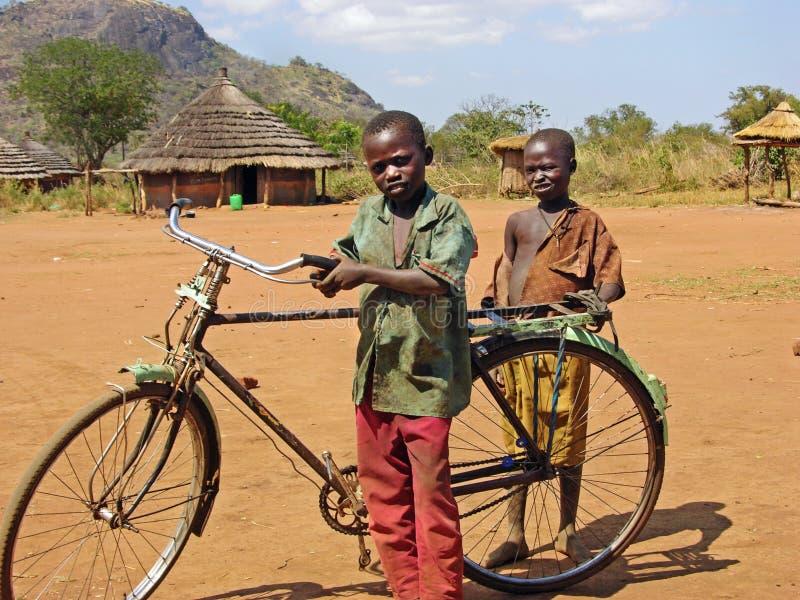 Pauvres enfants africains avec le village à distance Afrique de vieille bicyclette photo stock