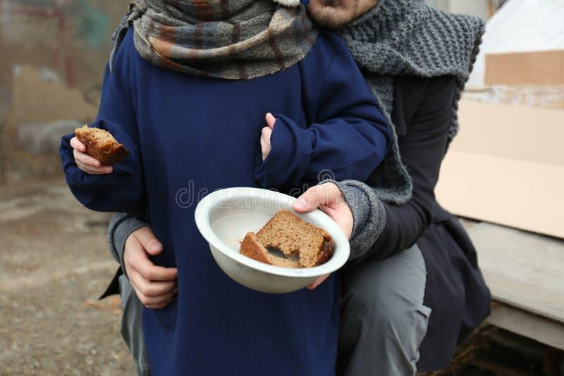 Pauvres père et enfant avec du pain à la décharge images stock