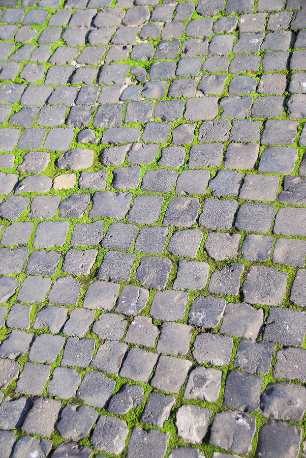 Pavés ronds romains et mousse verte images stock