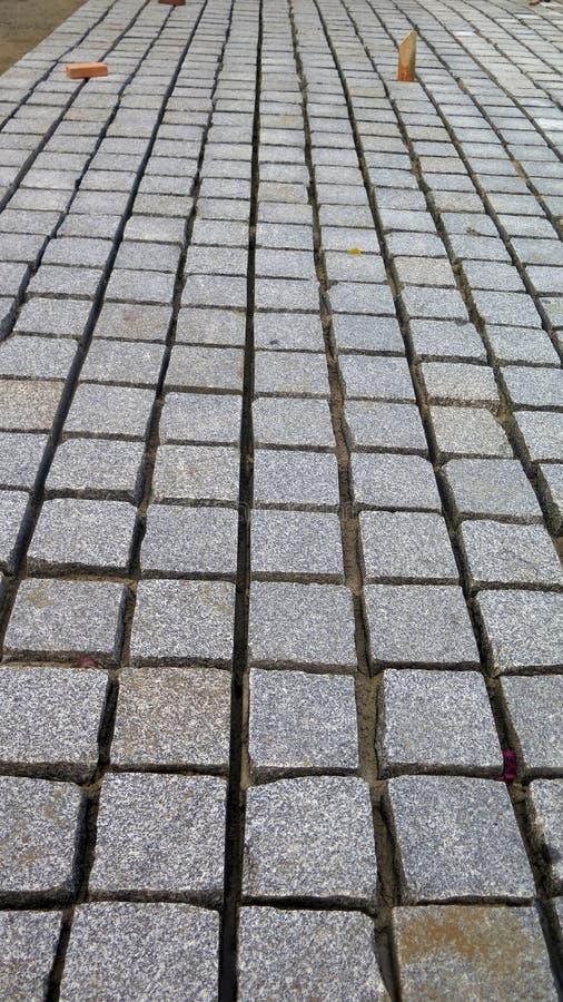 Pavage en pierre gris partiellement de finition de bloc photos stock