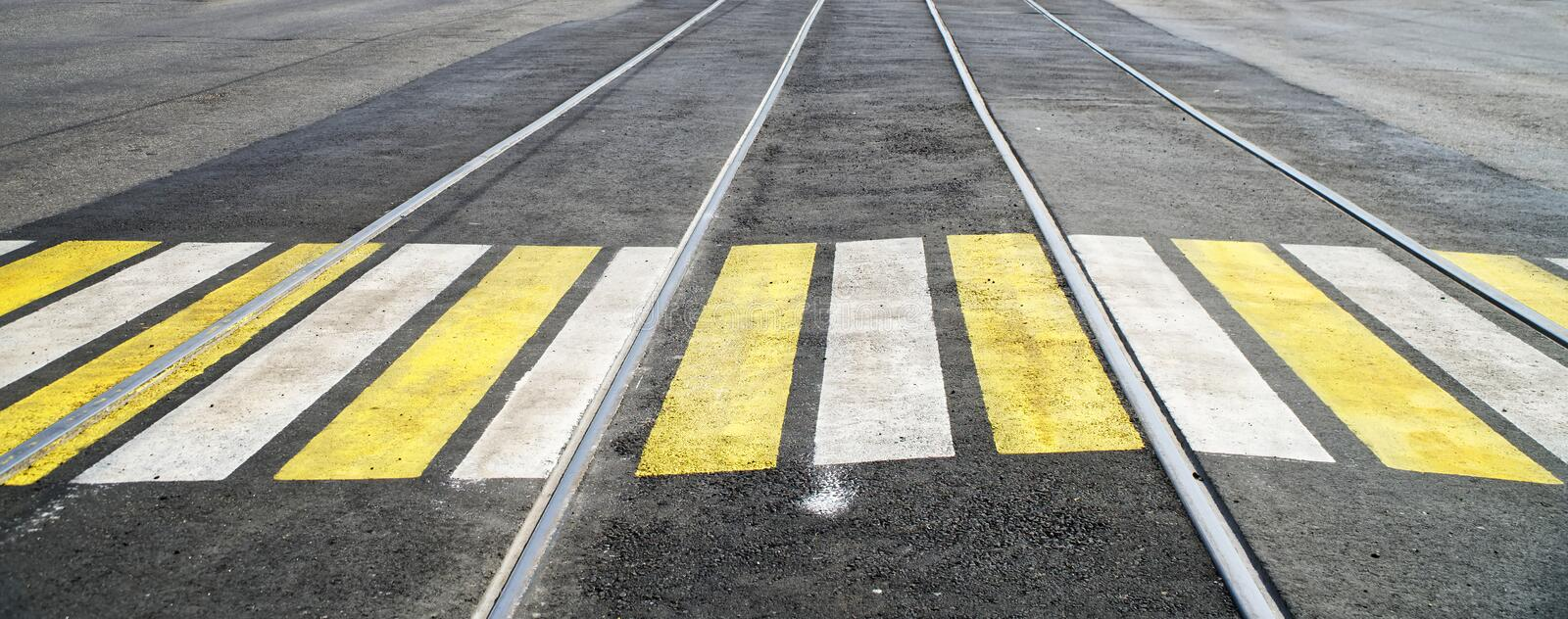 Paved crosswalk over tram rails, marked with white and yellow paint. Road safety. Urban economy stock photography