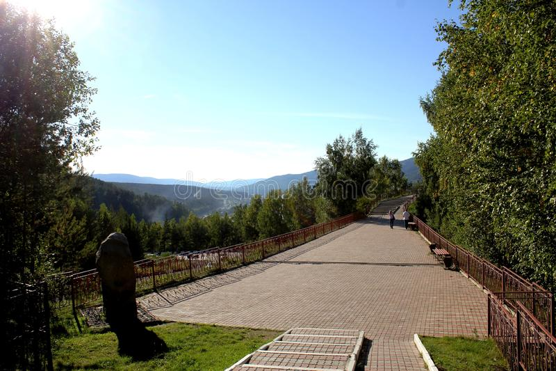 Paved footpath with mountain views. Beautiful summer day. Distant blue mountains royalty free stock photos