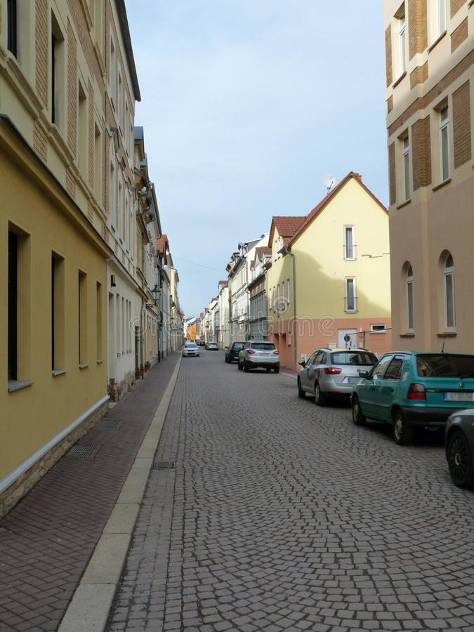 A paved road with houses and parked cars stock photography