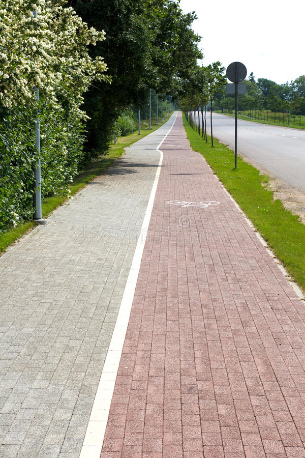 Paved sidewalk. With a bicycle path stock image