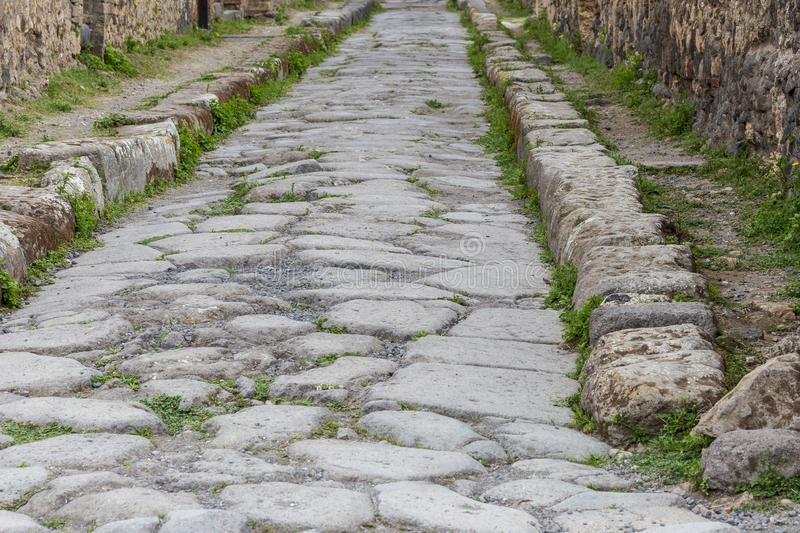 Paved street at  antique roman city of Pompeii, Italy. royalty free stock photography