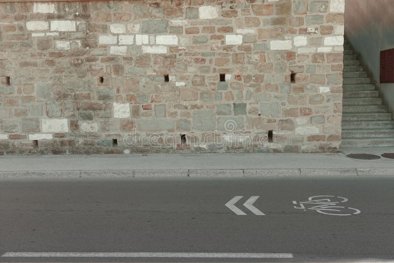 Paved street and wall. Side view of a paved street marked for bicycles, with a sidewalk, a mixed stone wall and concrete steps beside it royalty free stock photos