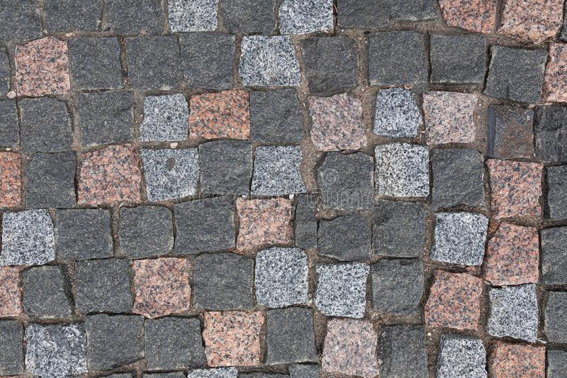 Pavement with colorful granite cobstone, background with grunge texture. Walkway paved with multicolored granite cobblestone, background with grunge texture stock photos
