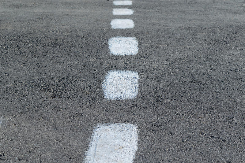 On the pavement marking. Rough intermittent white line. On the gray asphalt paint marking. Rough intermittent white line. Dashed markings divide the road in stock photo