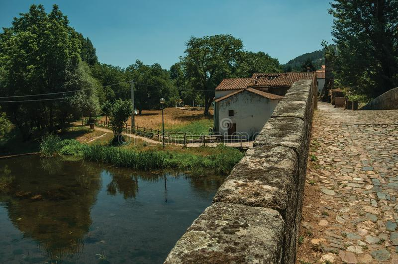 Pavement over an old Roman bridge and house in Portagem. Cobblestone pavement and breastwork over an old Roman bridge still in use over the Sever River among royalty free stock images