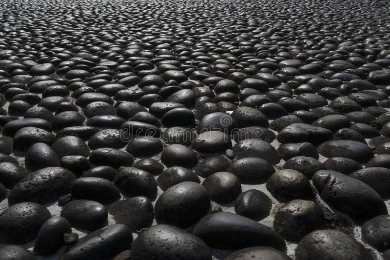Pavement with round black boulders stock photos
