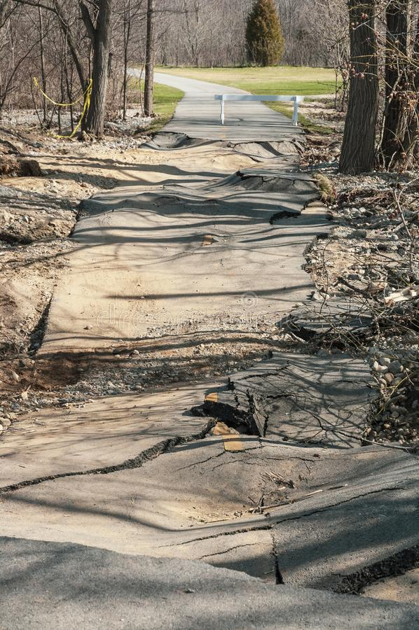 Pavement torn up by flooding on Blackstone River bike path. Broken and collapsed pavement along Blackstone River Greenway after severe rains stock photos