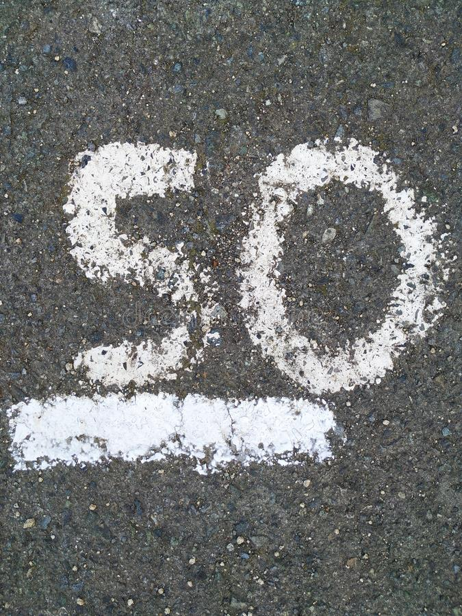 Onthe number 50 is written with white paint on the gray asphalt. royalty free stock photography