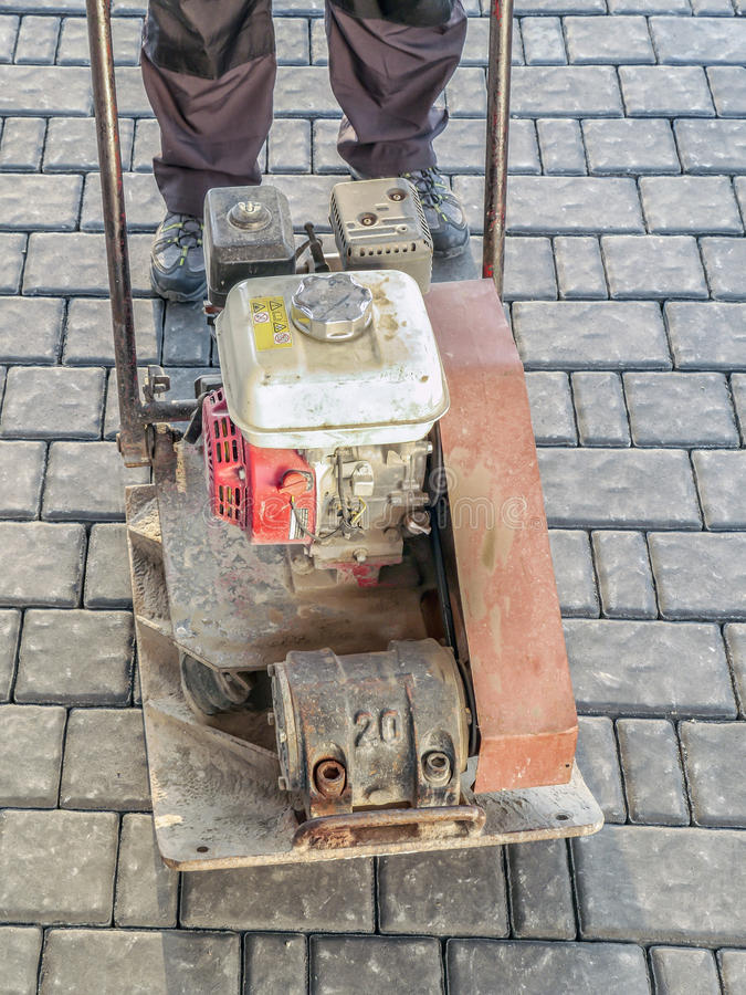 Paver with plate compactor stock images