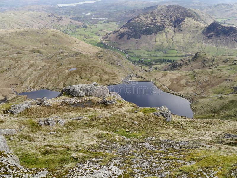 Looking down to Stickle Tarn from Pavey Ark, Lake District. On Pavey Ark looking down to Stickle Tarn with Windermere right at the back and Lingmoor Fell to the royalty free stock photos