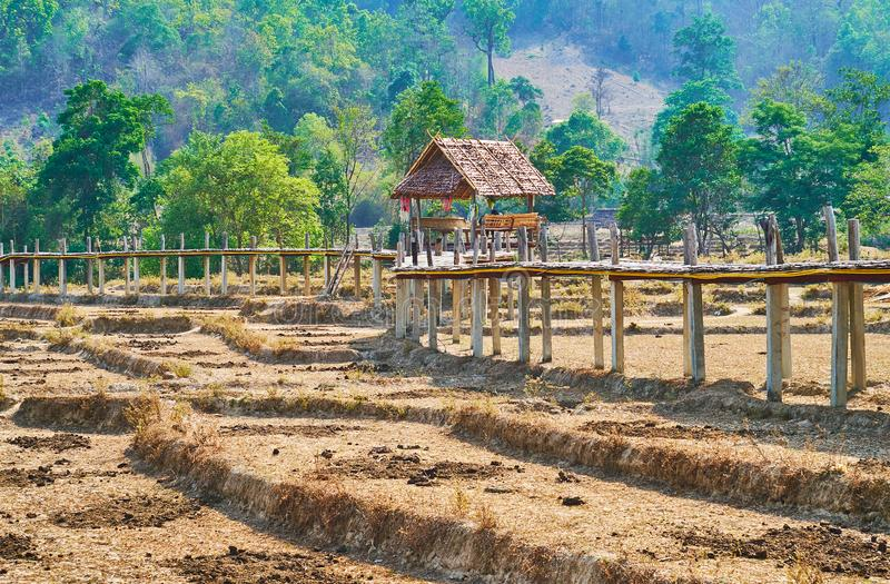 Pavilion on Boon Ko Ku So bamboo bridge, Pai, Thailand. The small wooden pavilion with benches on the Boon Ko Ku So bamboo bridge, surrounded by dried paddy royalty free stock photos