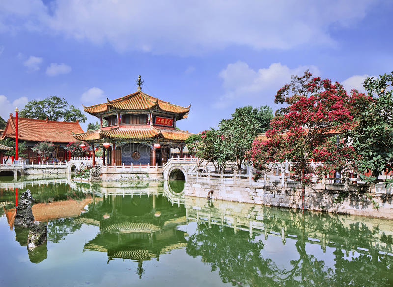 Pavilion mirrored in green pond, Yuantong Temple, Kunming, Yunnan Province, China. Ornate pavilion mirrored in green pond, Yuantong Temple, Kunming, Yunnan royalty free stock image