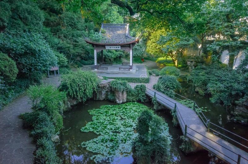 Paviljongen och bron över dammet i Zhongshan parkerar på den Gu kullen, nära den västra sjön av Hangzhou, Kina royaltyfria foton