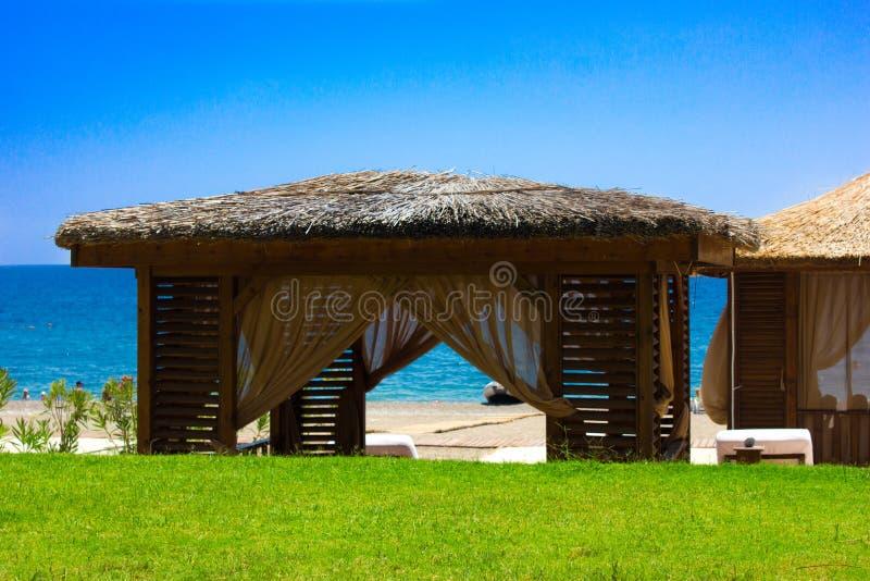 Pavillon mit einem Strohdach auf einem sandigen Strand Mittelmeersommer und Meer lizenzfreie stockbilder