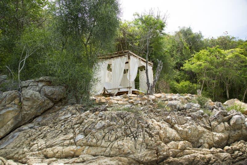 Pavillon sur une plage rocheuse photos stock