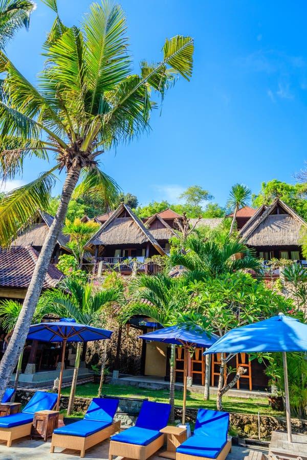 Pavillons en bois et chaises longues bleues avec des parapluies, Nusa Lembongan, Indonésie image stock