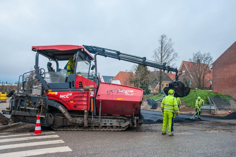 Pavimentadora que pone el asfalto en un nuevo camino con la ayuda de los trabajadores imagen de archivo