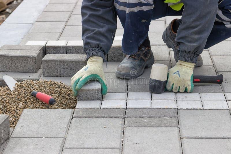 Pavimentazione del marciapiede della regolazione del muratore fotografie stock libere da diritti
