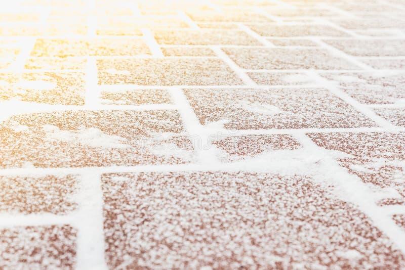 Pavimentazione delle mattonelle rosse sotto il gelo e la neve fotografia stock libera da diritti