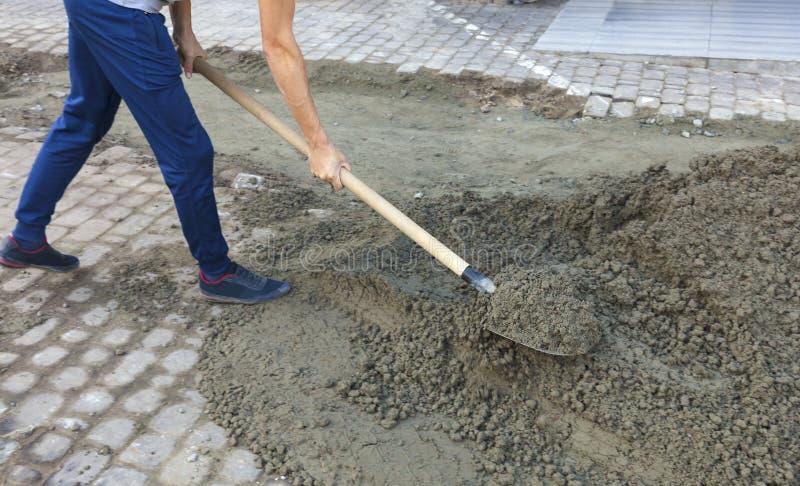 Pavimentazione delle mattonelle sul marciapiede, il lavoratore che livella il fondamento con una pala della costruzione fotografia stock