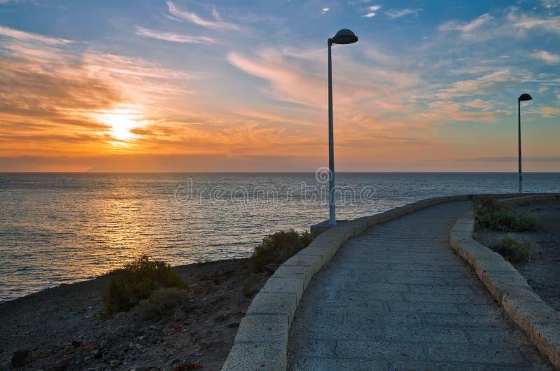 Pavimentazione di pietra lungo il mare al tramonto fotografia stock libera da diritti