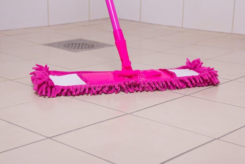 Pavimentazione in piastrelle rosa di pulizia di zazzera in bagno