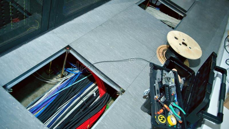 Pavimento alzato & x28; floor& smontabile x29; nella stanza del server con una covata aperta sopra alla covata sono i cavi della  fotografia stock