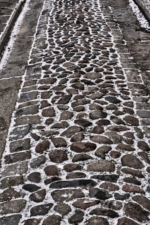 Pavimento de fusión de la nieve y del tobillo en el stree fotografía de archivo