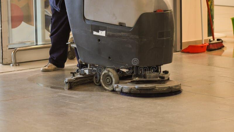 Pavimento del deposito di pulizia del lavoratore con la macchina immagine stock libera da diritti